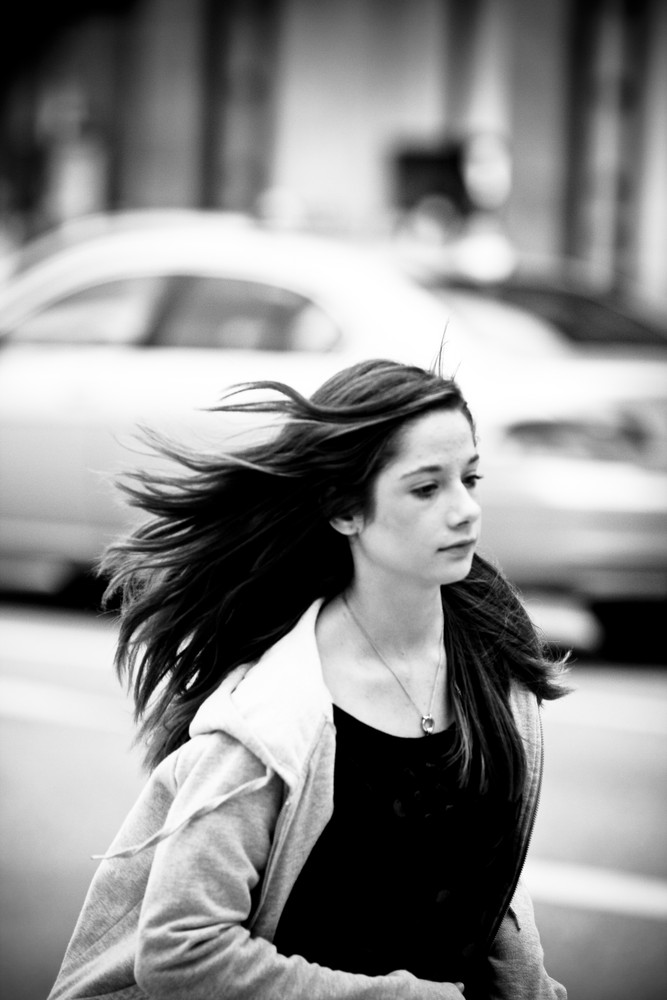 long hair. windy. she. moving. car in the back...