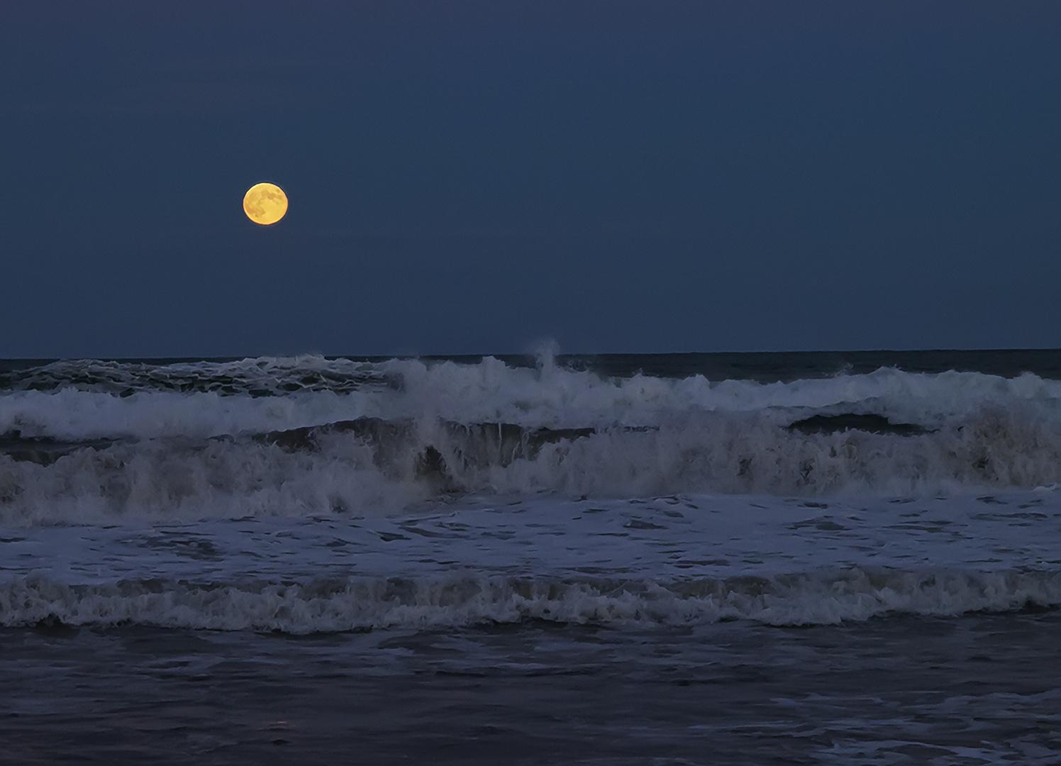 Luna llena sobre las olas.