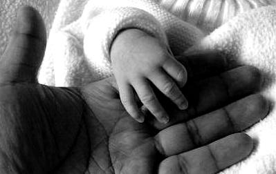 Lyanna main dans la main avec son papa, le 1er jour de sa vie.
