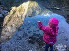 Mädchen ist begeistert über die Berge auf dem Wasser