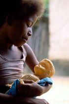 Mädchen mit Puppe im Arm an der Haustür
