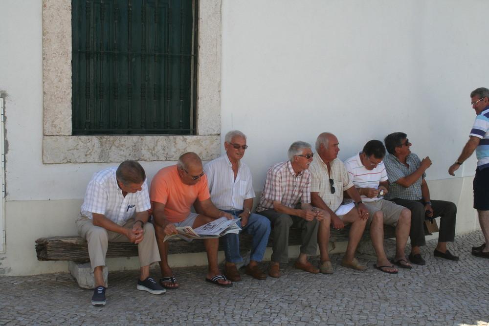 Männer sitzen und warten in Alcochete