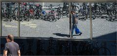 Mann im Spiegel, eine blaue Stofftasche tragend...