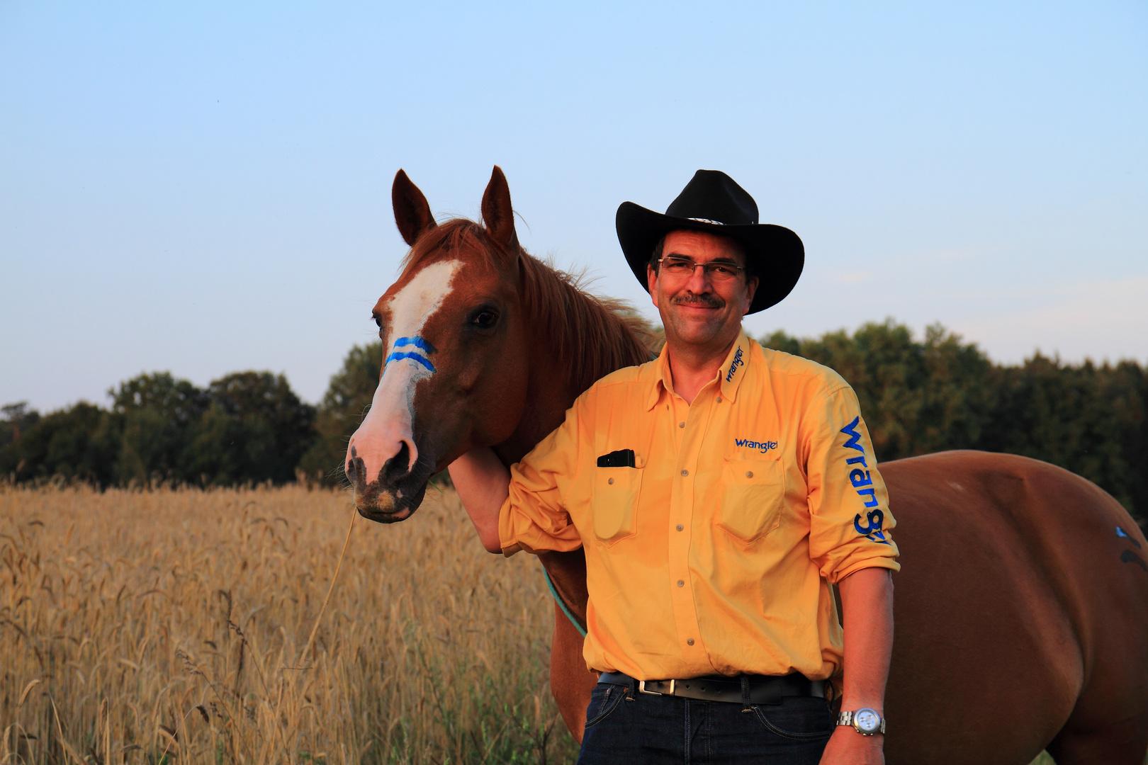 Mann mit paint horse auf dem Feld 2014 Spätsommer