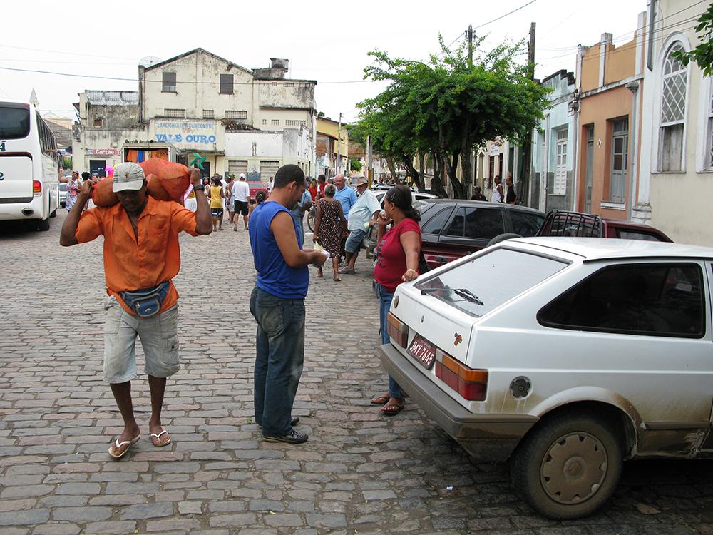Mann trägt einen Sack auf dem Rücken durch Cachoeira