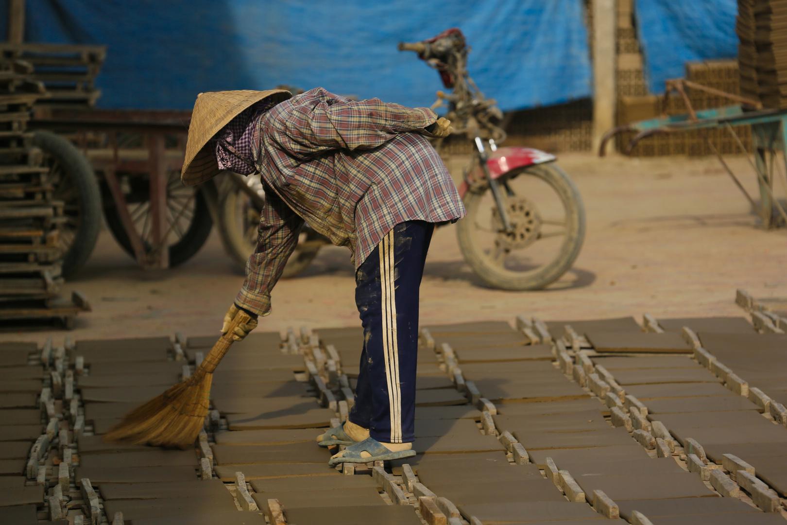 Mekong, Arbeiterin putzt Fliesenrohlinge