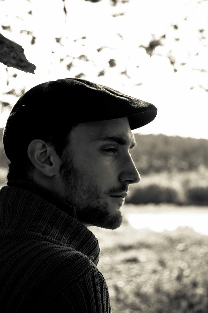 Mensch mit Bart ernst am Fluss