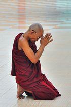 Monk praying to the Buddha in Botataung Pagoda in Rangoon