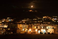 Moon setting over ornos town in Mykonos