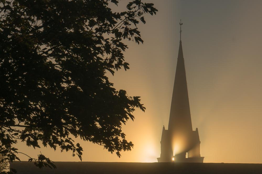 Morgendämmerung hinter einer Kirche in der Bretagne