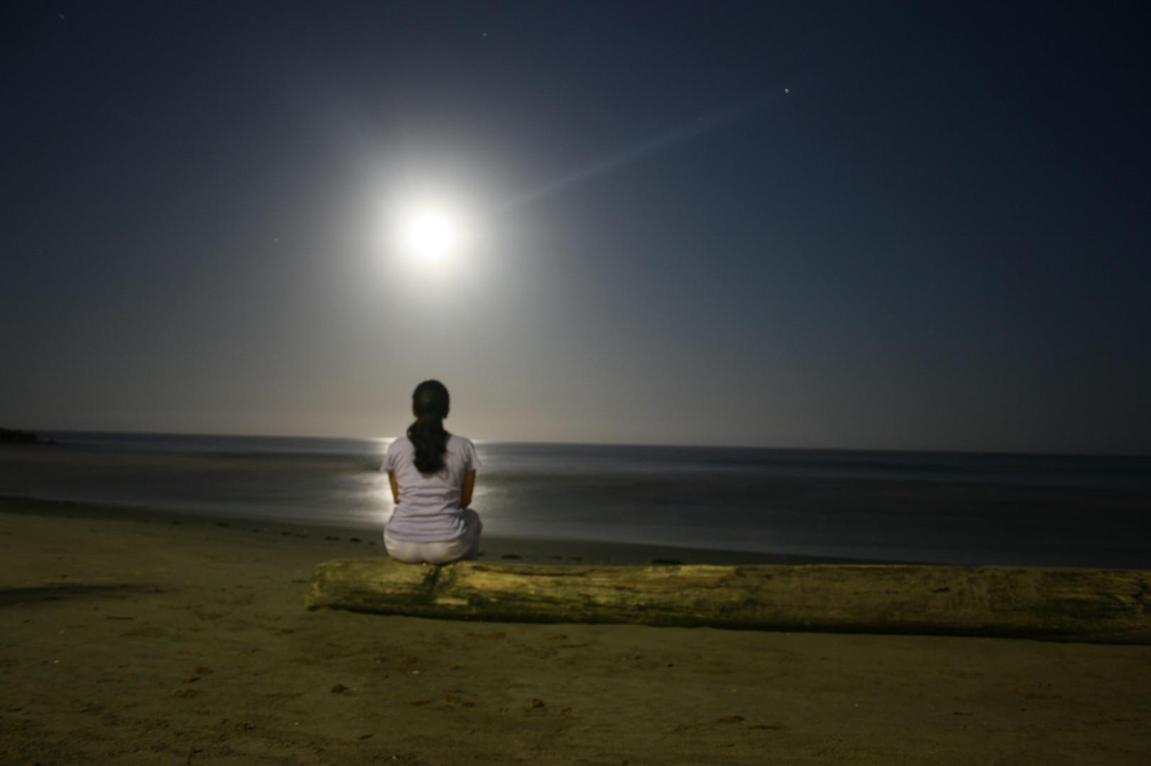 Mujer sentada en la playa viendo la luna