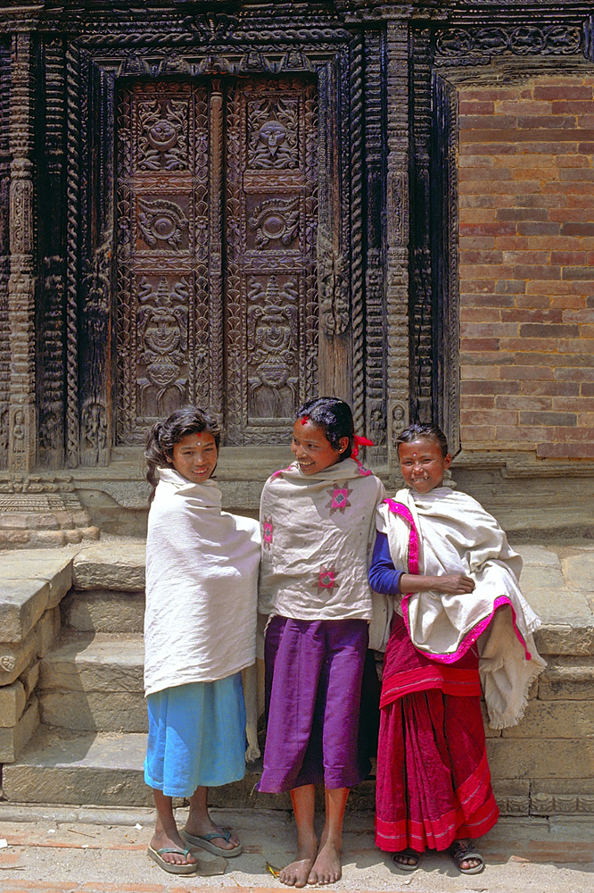 Newa girls in front of a carved gate in Bhaktapur