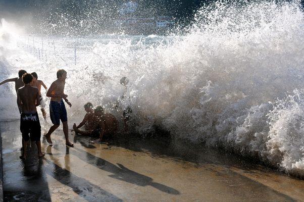 Niños jugando con las olas en verano en la playa de Zarautz