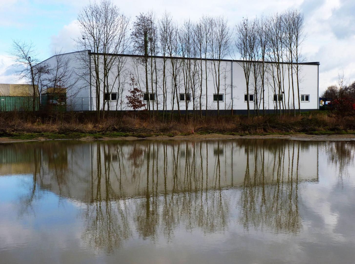 Nüchterne Industriearchiteltur hinter einer Wasserpfütze