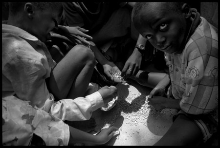 Partage des graines tombées pendant la distribution par les orphelins n'ayant rien reçu
