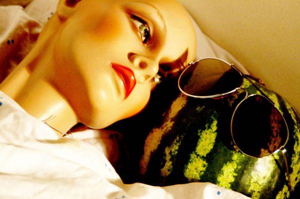 Puppe mit Melone im Bett