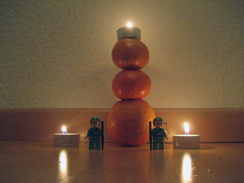 Rebbelen bewachen einen Turm aus Orangen Und Kerzen daruf