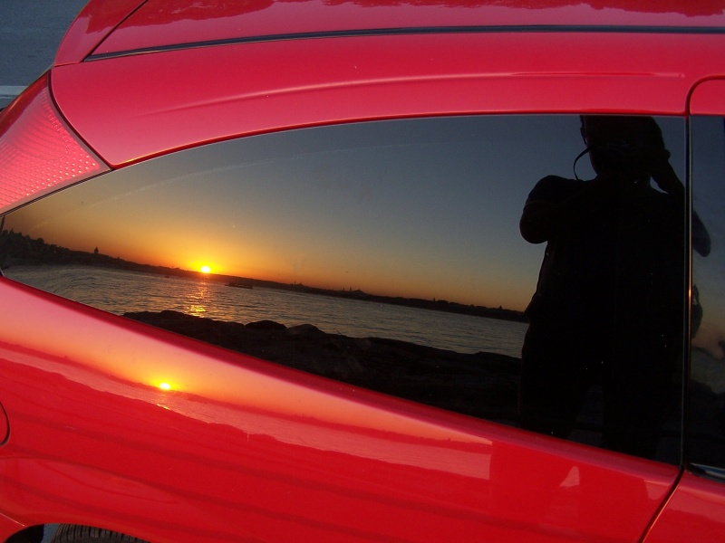 Red car and photographer in sunset.