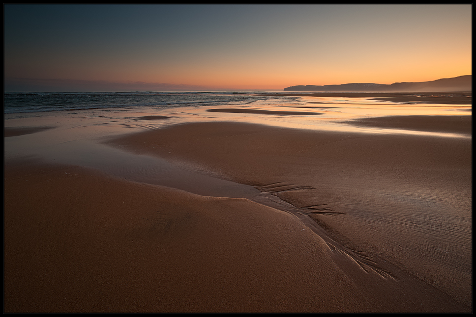 [ ... red sand beach ]