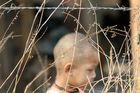 Refugee child behind barbed wire