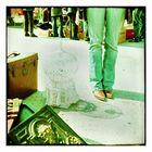 Relief , antiker Koffer , kitschiger Vogelbauer und Westernstiefel mit Beinen in Jeanshose dran