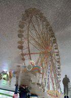Riesenrad in Wasserpfütze