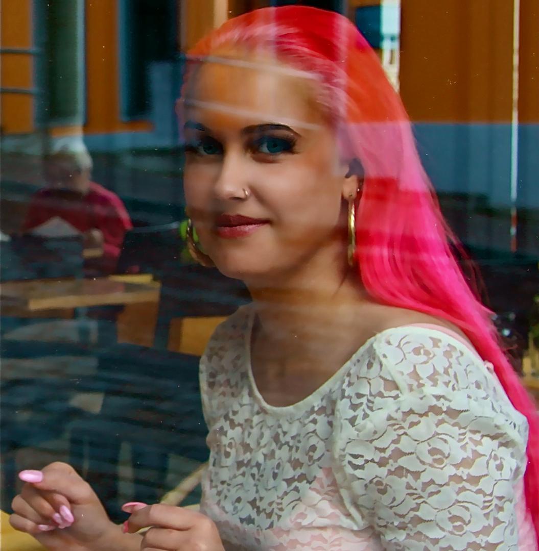 .... rosa Fingernägel hinter der Scheibe eines Kaffee's