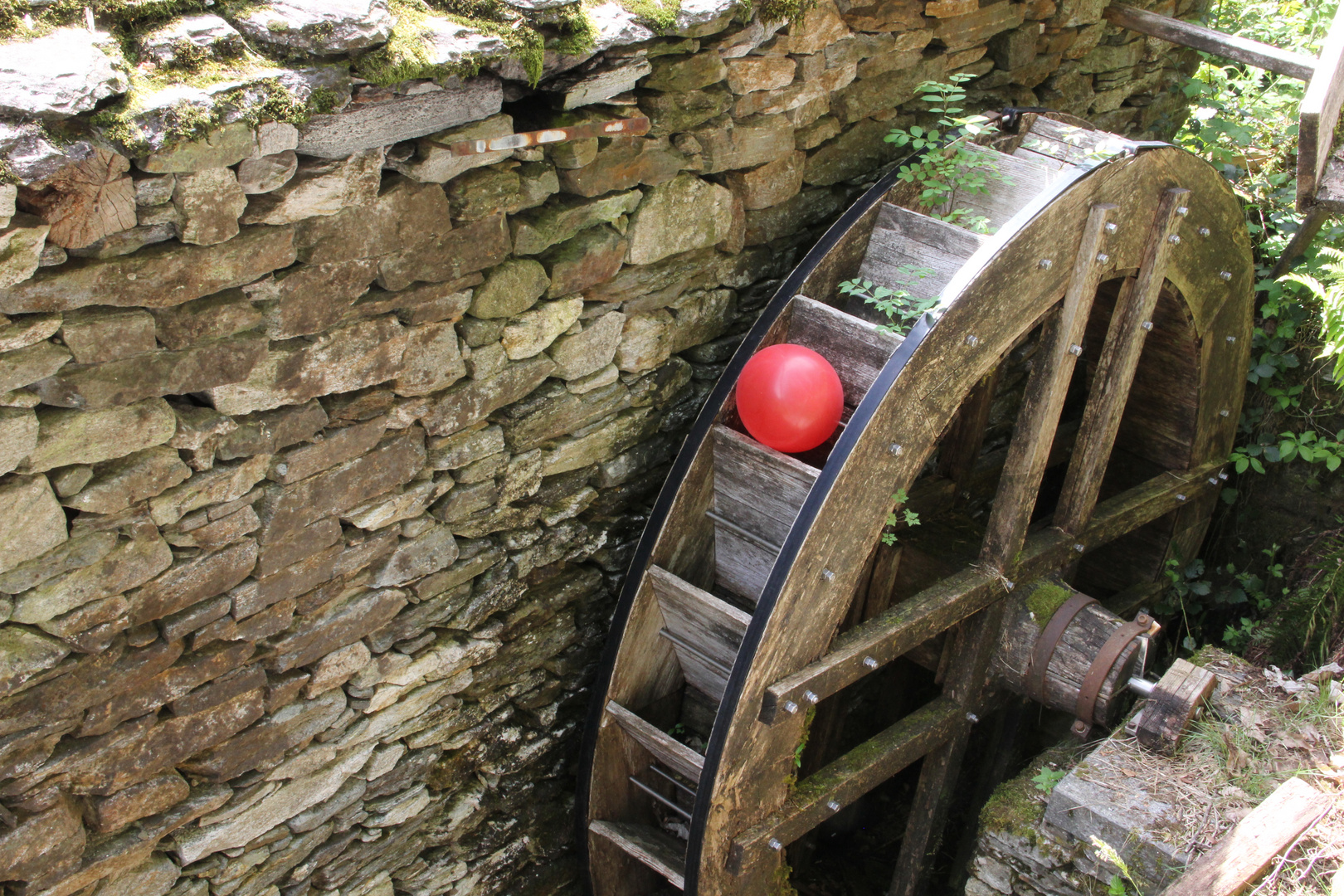 Roter Ballon im Wasserrad