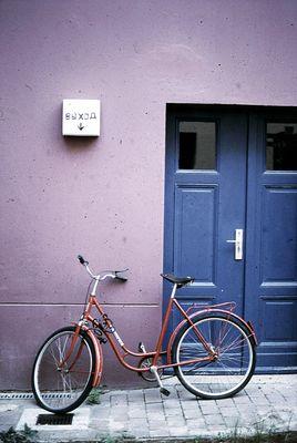 rotes fahrrad, blaue tür, lila wand