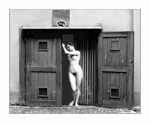 schiefe Nackte lehnt an schiefer Tür und schaut schief..