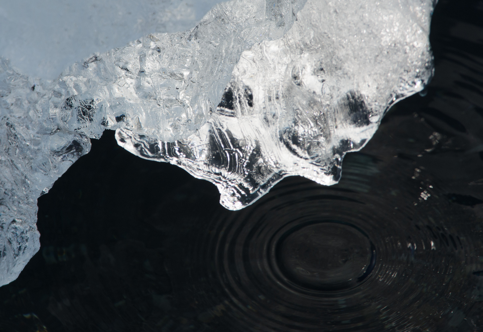 Schmelzendes Eis am schwarzen Strand