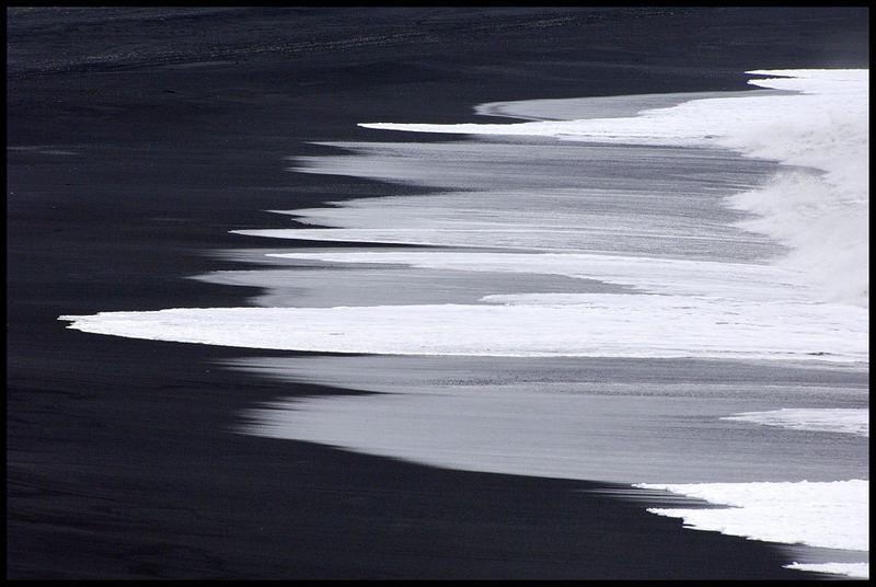 Schwarzer Strand und weiße Gischt