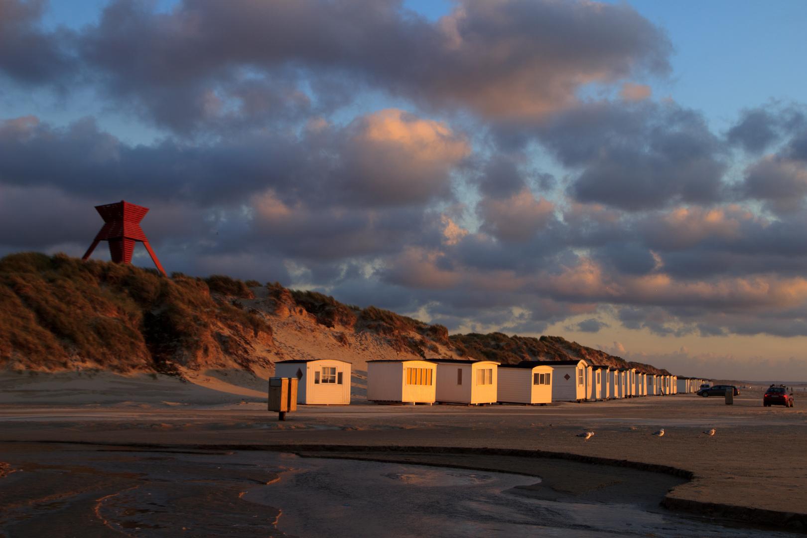 Seezeichen und Badehäuser bei Sonnenuntergang