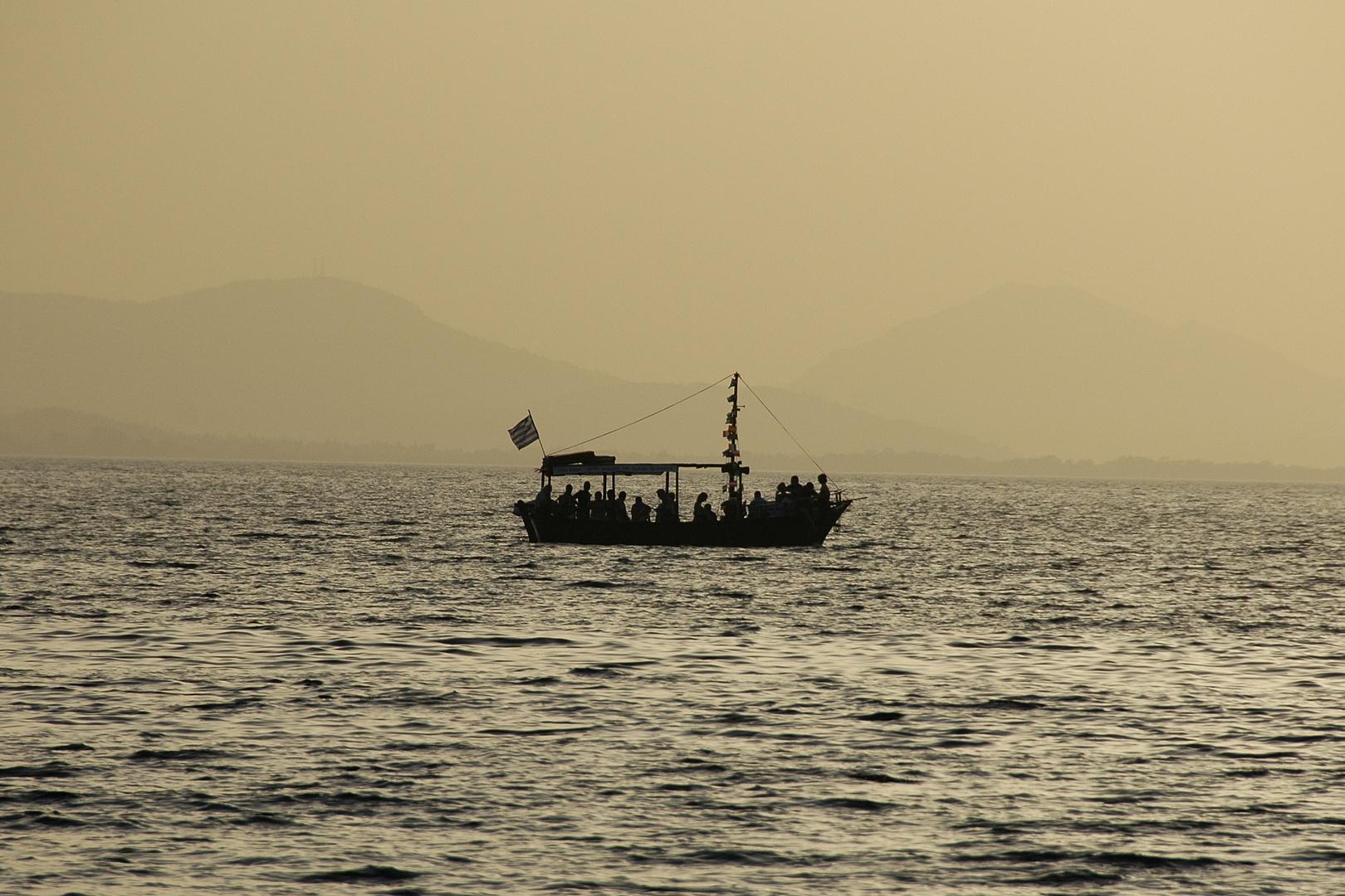 """""""Sirtaki""""-Boot vor der untergehenden Sonne im ionischen Meer"""