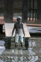 Sitzender Junge am Bootssteg