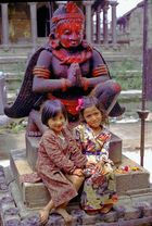 Small Newa girls in Lalitpur in front of Garuda statue