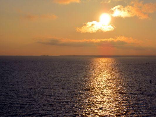 Sonne hinter Wolke überm Meer