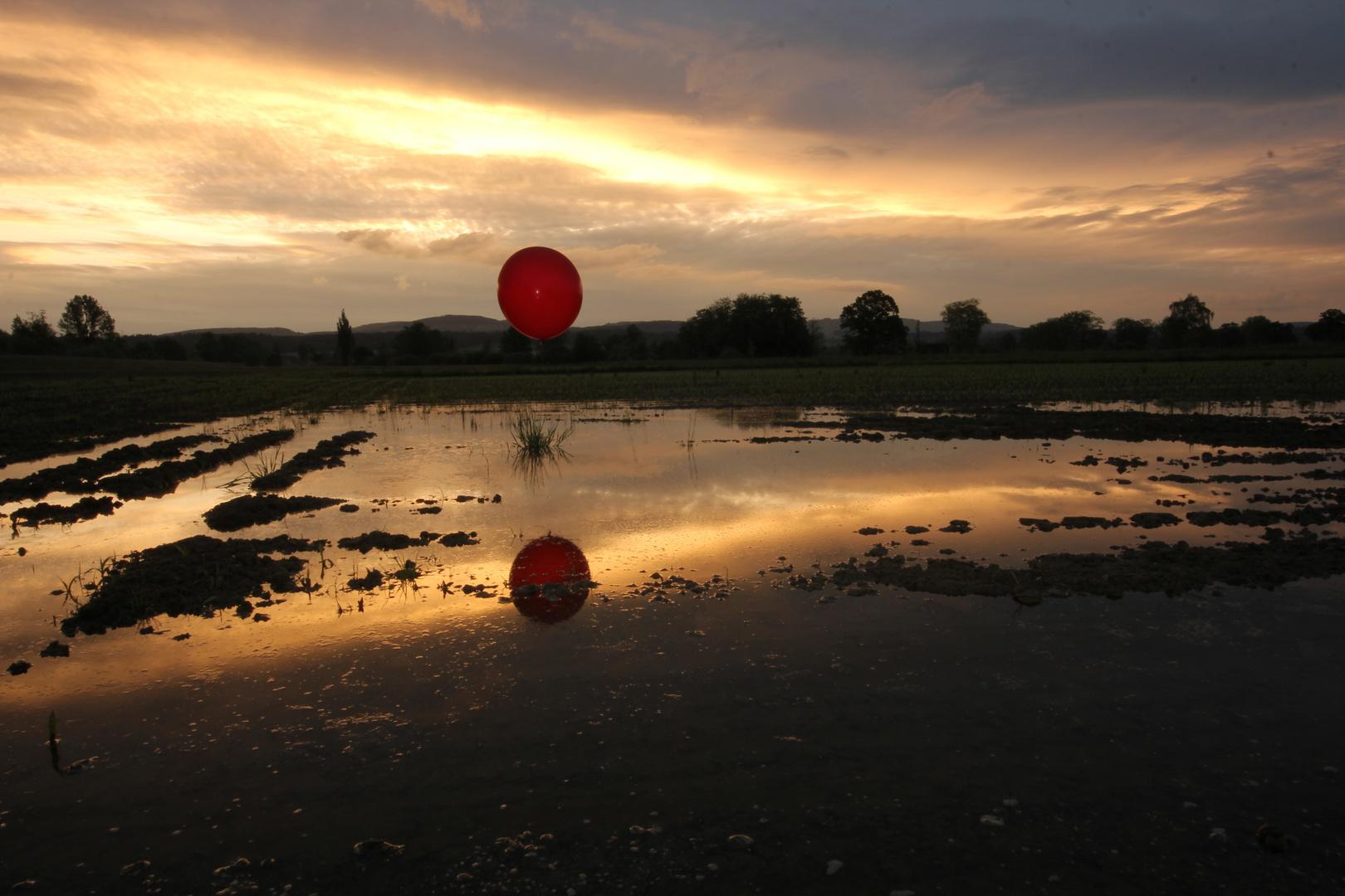 Sonnenaufgang mit rotem Ballon