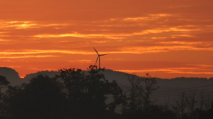 Sonnenaufgang mit Windrad