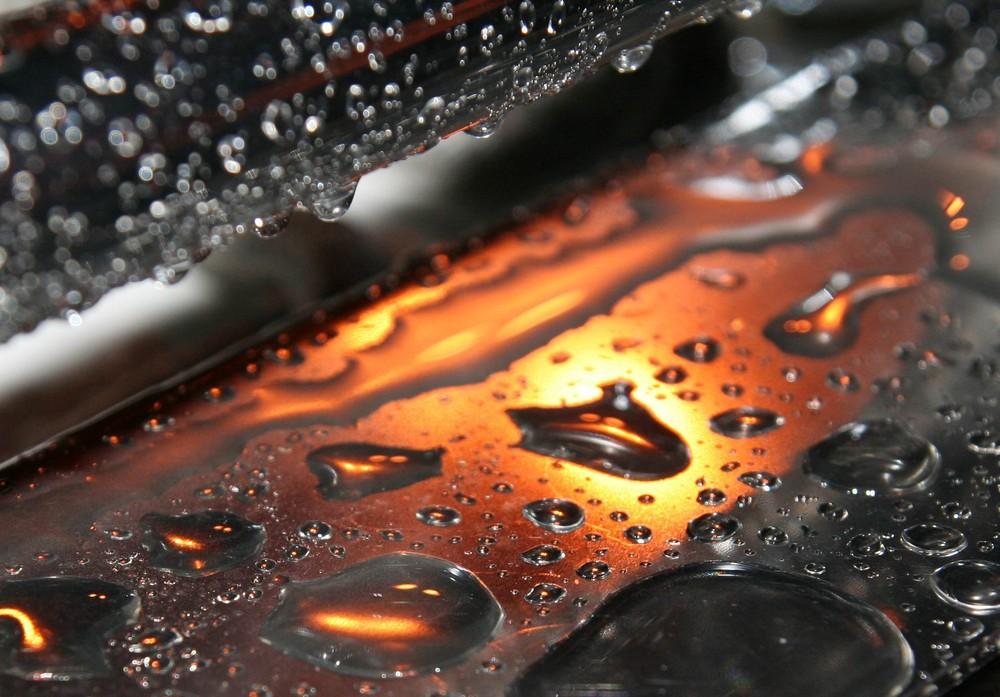 Sonnenuntergang auf Stahlplatte mit Wassertropfen gespiegelt