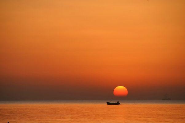Sonnenuntergang oder Sonnenaufgang mit Boot, Meer