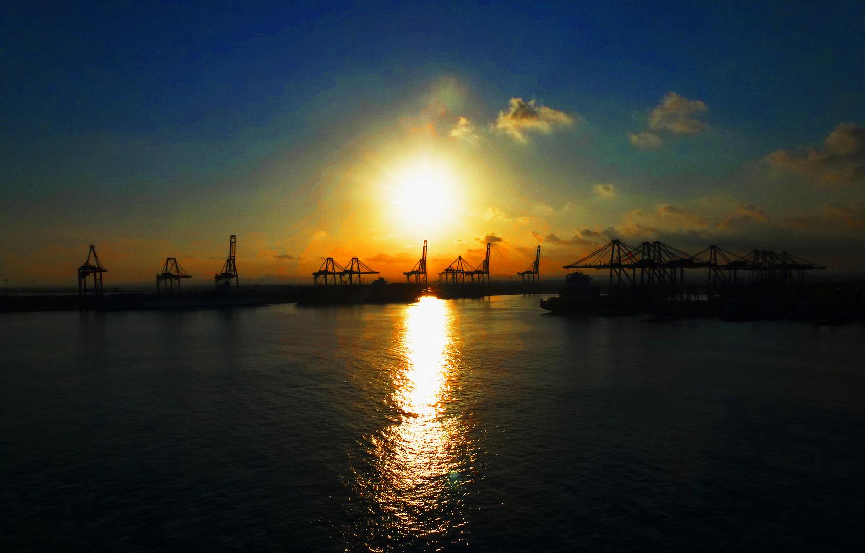 Sonnenuntergang über spanischen Hafenkränen