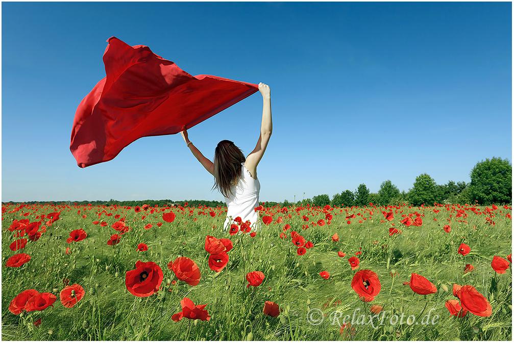 """""""Spiel mit dem Wind"""" - Junge Frau in weißem Sommerkleid mit wehendem rotem Tuch in Mohnfeld"""