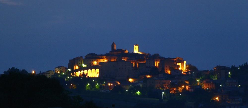 Stadt mit Abendbeleuchtung in der Marche