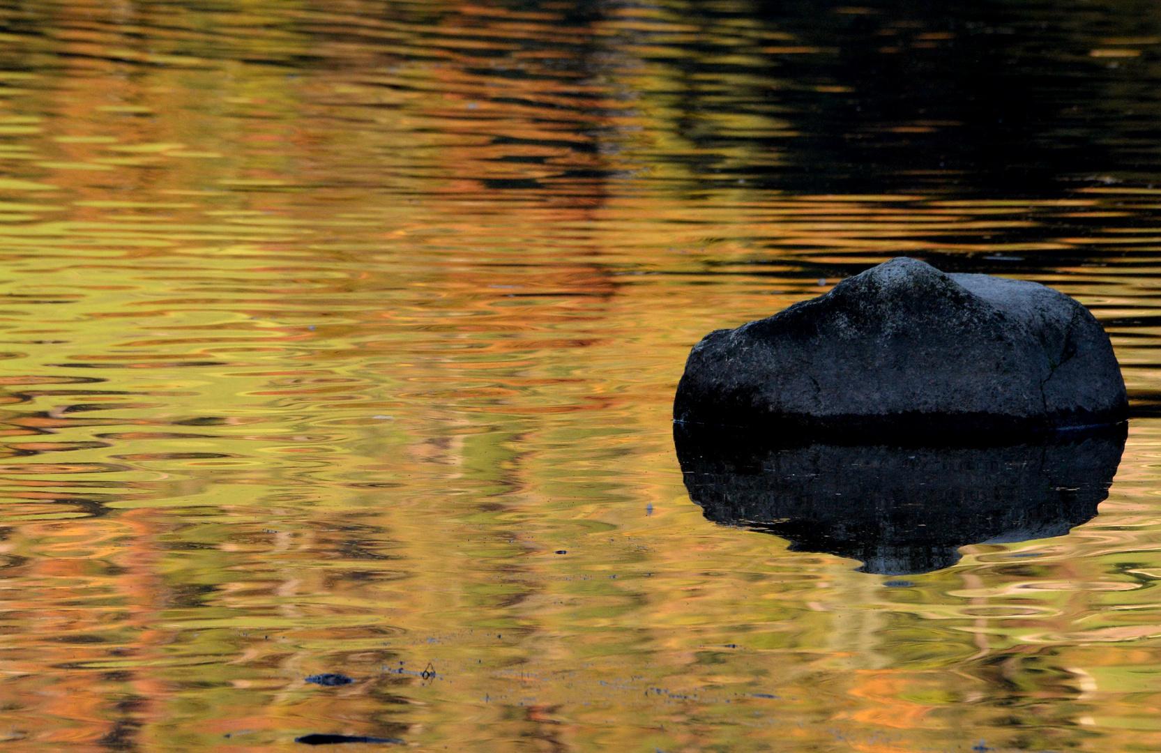 Stein im Wasser bei Sonnenuntergang