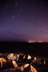 Steine am Meer und der Sternenhimmel über Ustka (Polen)