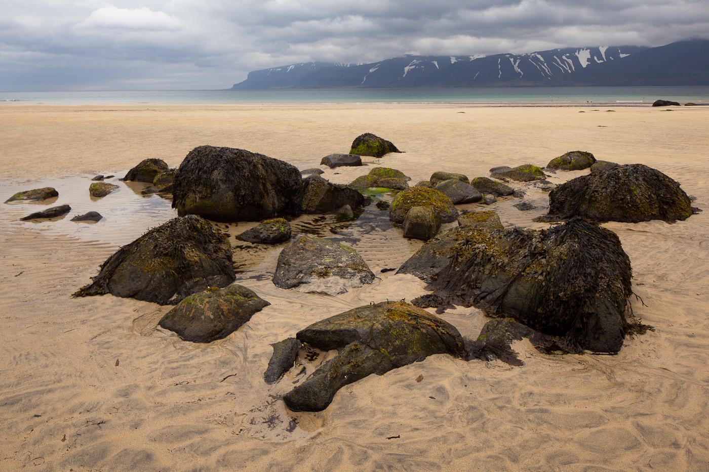 Steine, Strand und bewölkter Himmel