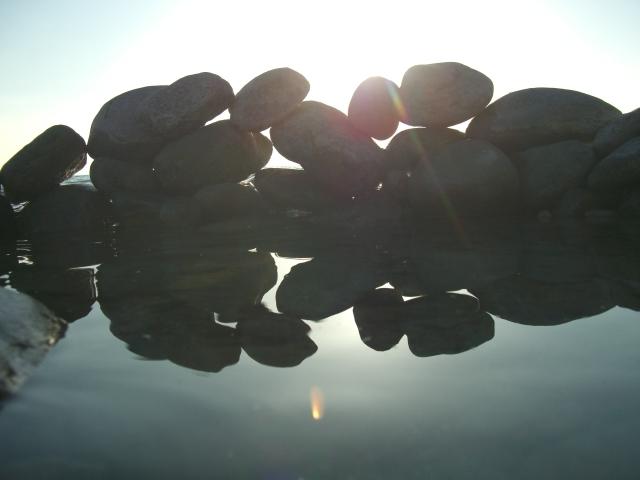 Steine und ihre Spiegelungen im Wasser