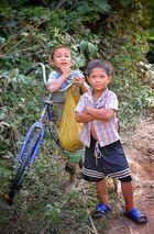 Stolze Fahrradbesitzer in einem Dorf am Nam Ou River