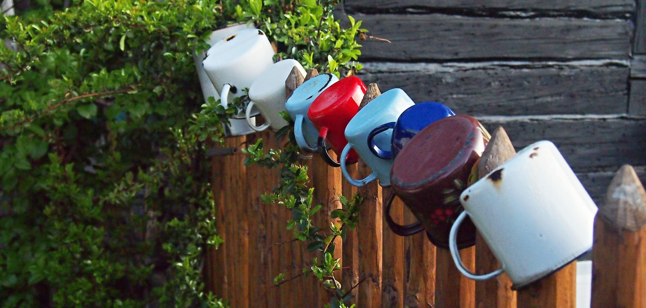 Tassen auf dem Zaun